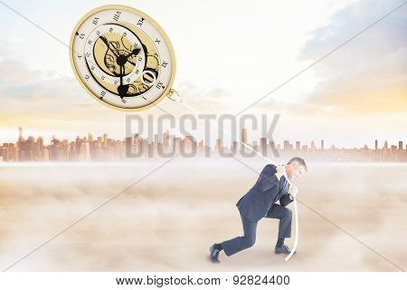 Classy businessman pulling a rope against city on the horizon