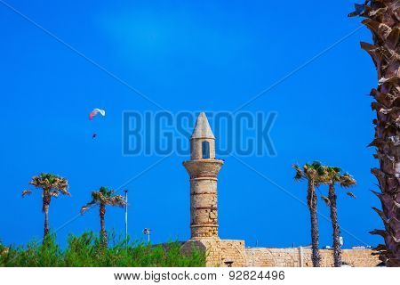 Palm tree, minaret and parachute.  National park Caesarea on the Mediterranean Sea