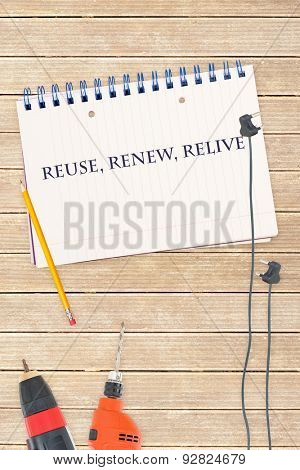 The word reuse, renew, relive against tools and notepad on wooden background