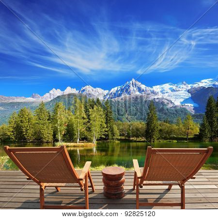 City park in the Alpine resort. Comfortable lounge chairs on wooden platform for rest and observation