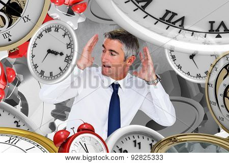 Businessman looking up with arms up against grey background