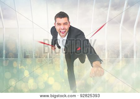Businessman crossing the finish line against room with large window looking on city