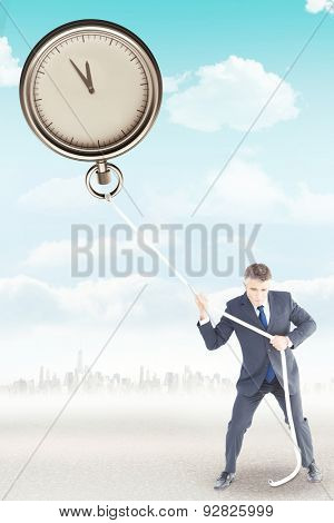 Businessman in suit pulling a rope against city on the horizon