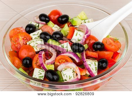 Transparent Glass Bowl With Greek Salad And Plastic Spoon