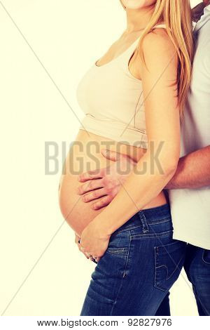 Father embracing her wife's pregnancy belly