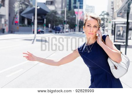 Businesswoman trying to catch a taxi in business cuty district