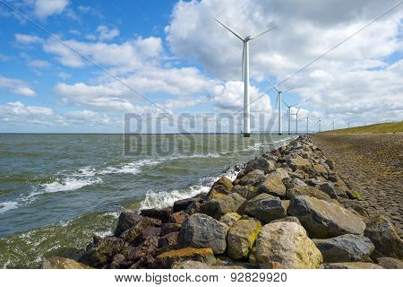 Wind farm in water along a dike in spring