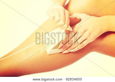 Close up on woman shaving her leg.