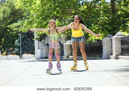 Young mom with her 6 years old child rollerskating in park
