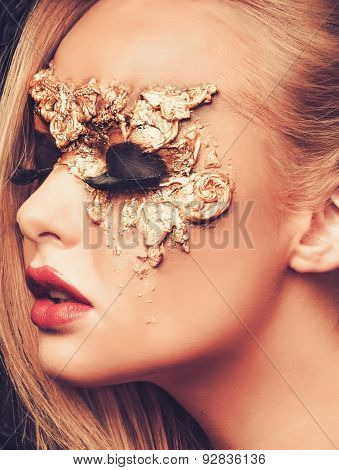 Woman with creative carnival mask on her face
