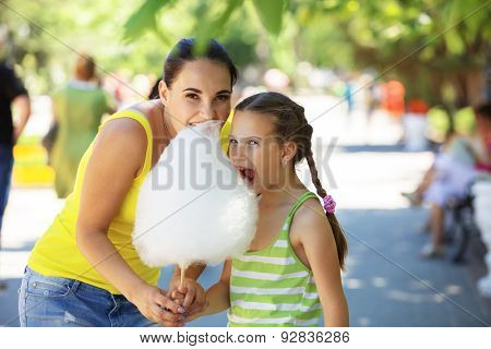 Child eats cotton candy with mom in city street