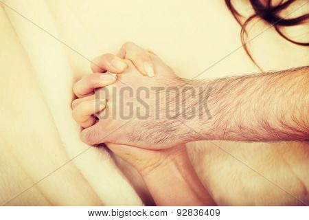 Hands of playful couple lying on bed.