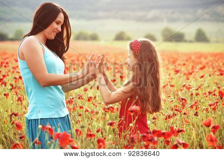 Mother and her 7 years old preteen child playing in spring poppy field in soft sunlight