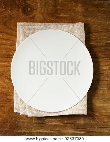 empty plate with cutlery and napkin on wooden background