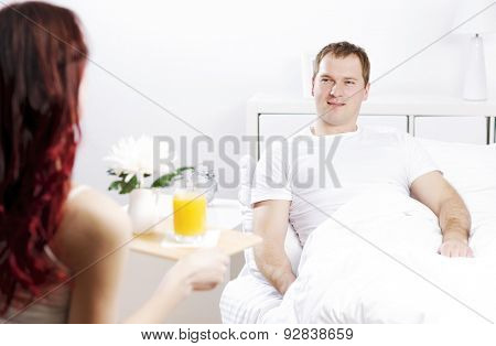 Beautiful young couple having breakfast in bed