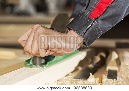 Close up of carpenter hands working with plane in his studio