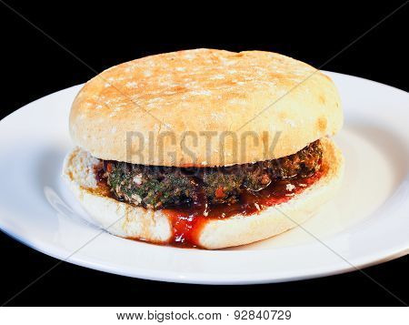 Closeup Of Juicy Hamburger Between Buns With Delicious Red Sauce On White Plate Towards Black