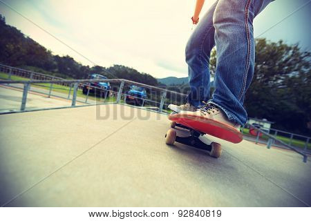 skateboarder legs riding on skateboard at skatepark ramp