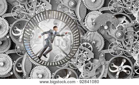 Young businessman running in wheel of gears mechanism