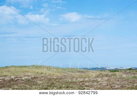 Wind turbines in rocky coastal ocean landscape