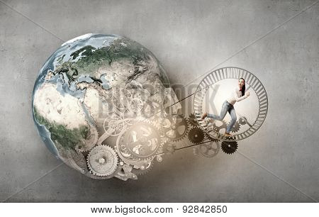 Young businesswoman running in wheel of gears mechanism. Elements of this image are furnished by NASA