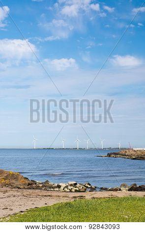 Wind turbines in rocky coastal ocean landscape