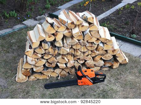 Stabel Of Chopped Birch Wood And Chainsaw