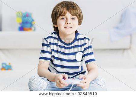 Boy sitting on floor and palying with joystick