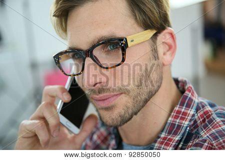 Trendy guy with eyeglasses talking on phone in office