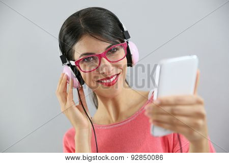 Brunette girl listening to music on smartphone, isolated