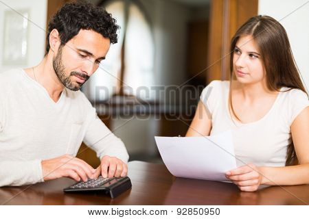 Young couple calculating their expenses. Shallow depth of field, focus on the man