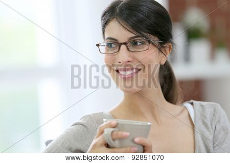 Portrait of brunette girl with eyeglasses holding cup of tea