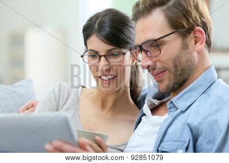 Couple with eyeglasses websurfing on tablet at home