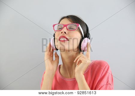Clsoeup of brunette girl with eyeglasses using headphones