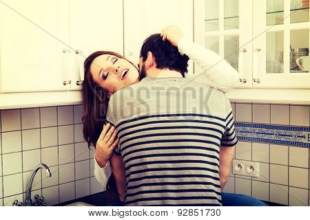 Young couple kissing with desire in the kitchen.