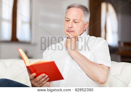 Mature man reading a book on his sofa