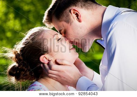 Young romantic couple kissing with love in summer park. Dating, fiance with fiancee, romance.