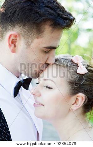 Young handsome man embracing and gently kissing his fiancee outdoors. Date, fiance with fiancee, couple in love.