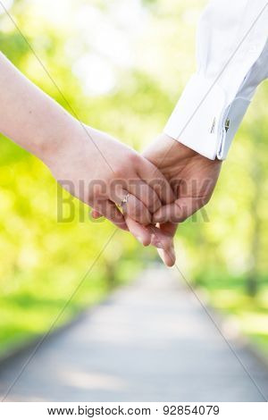 Holding hands close-up. Couple in love dating in summer park. Woman in dress and man wearing elegant shirt. View from the back. Date, fiance with fiancee, hand in hand concepts
