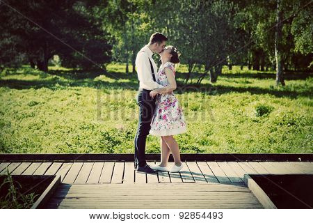Young couple in love standing on wooden cross-roads in summer park. Woman in dress and man wearing shirt with suspenders.