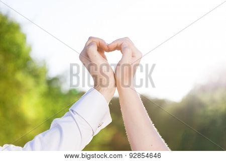 Couple in love making a heart shape with their hands outdoors. Man wearing elegant white shirt with cufflinks.