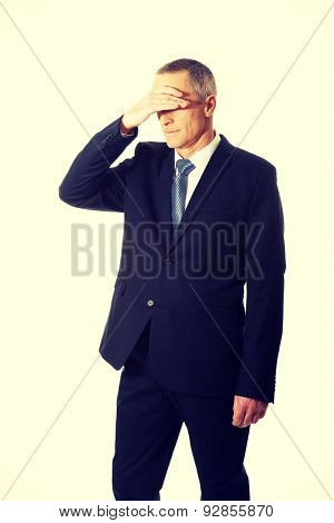 Stressed businessman covering his face.