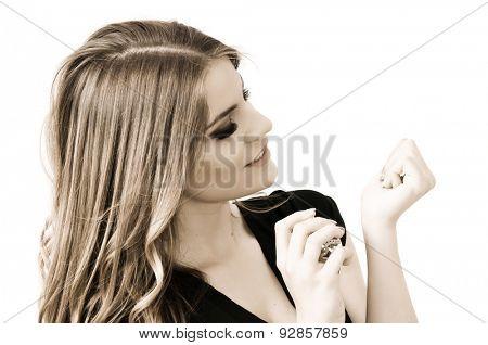Beautiful teenage girl applying perfume on her hand, isolated on white