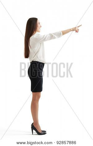 full length portrait of smiley woman in formal wear pointing up finger and looking the same direction. isolated on white background
