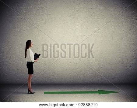 sideview of smiley woman standing near green arrow on the floor in grey concrete room with empty copyspace on the wall