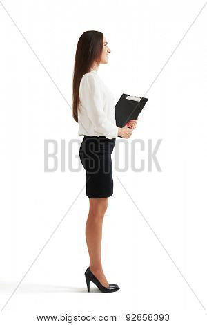 sideview full-length portrait of smiley woman in formal wear holding folder and looking forward. isolated on white background