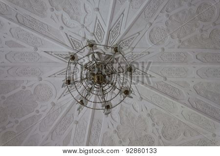 Chandelier and ceiling detail in a white room
