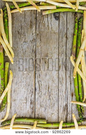 Asparagus -  white and green asparagus on wooden background, frame - space for text