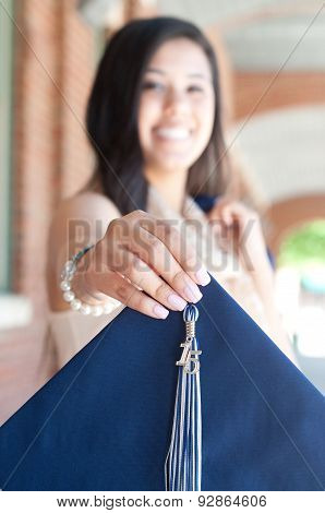 Beautiful High School Graduate Holding Out Graduation Hat.