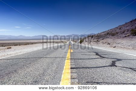 Long Distant Highway Under The Summer Sun Across Death Valley National Park